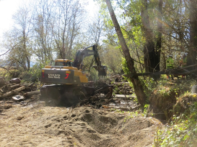 A Caltrans Heavy Equipment Operator uses an  excavator to remove debris from the confluence of Outlet and Davis Creeks.
